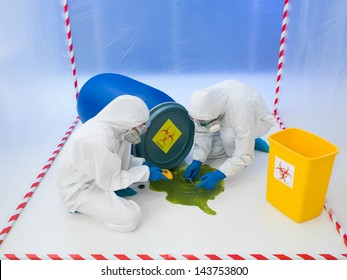 Two scientists in full protective biohazard suits attending to a biohazard chemical spill of green liquid from an overturned drum taking samples and performing tests in a containment tent