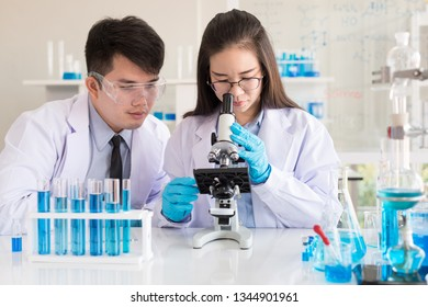 Two scientists working together at the research center using a microscope. chemists working with blue liquids in tubes at The Chemical Research Lab.