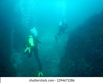 Two scuba divers exploring the bottom of Julian Rocks between reefs and walls - NSW