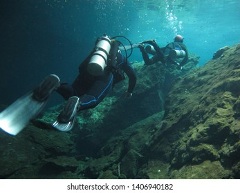 Two scuba divers exploring underwater cenote Chac Mool in the Riviera Maya, Mexico.