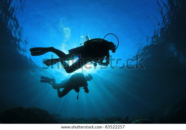 Two Scuba Divers, silhouettes against sunburst, in the ocean beside coral reef