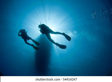 two scuba divers silouetted