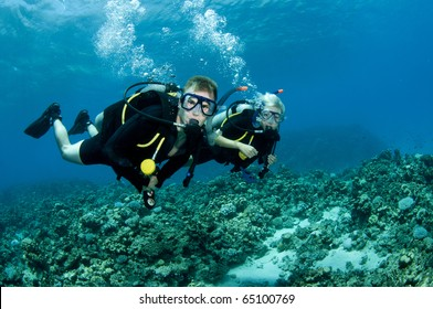 two scuba divers swim on a pristine coral reef in Ocean