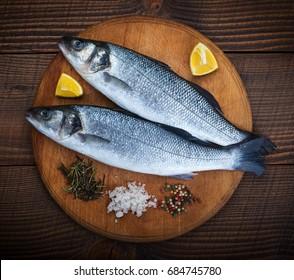 Two sea bass fish on cutting board