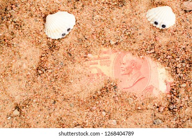 Two sea shells with googly eyes, lie on the sand and look at an old Soviet banknote. 10 rubles USSR with Lenin portrait close-up.