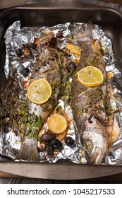 two seabass fish baked in the oven or on the grill, on a wooden table, protvin