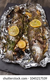 two seabass fish baked in the oven or on the grill, on food foil, on black slate