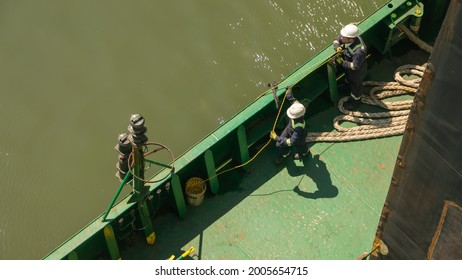 Two seafarers pulling and holding the mooring line during mooring of cargo ship