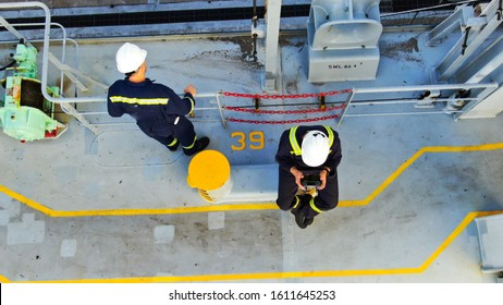 Two seaman on deck of container ship wearing boiler suit and helmets.