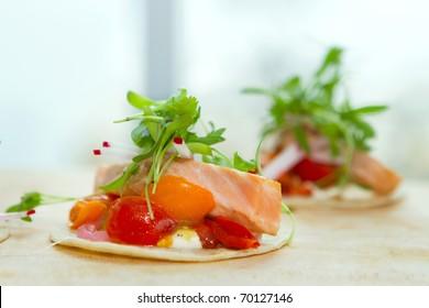 two seared salmon taquito wraps on a cutting board