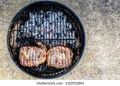 Two seasoned steaks sitting over coals on a small outdoor grill.