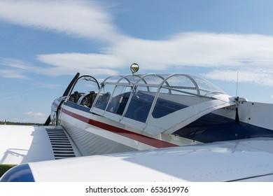 Two seat single engine civil utility aircraft, white small plane, red and blue strip is towed by a glider on a sunny day.