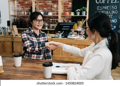 two seated asian women shaking hands in coffee shop smiling. hr lady manager welcome new employee to team after interview in cafe bar. female freelancers in glasses handshaking closing deal meeting
