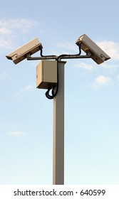 Two security cameras against a blue sky.