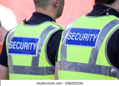 Two security guards on patrol, seen from behind