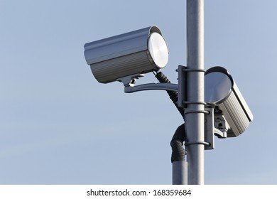 two security surveillance cameras on post