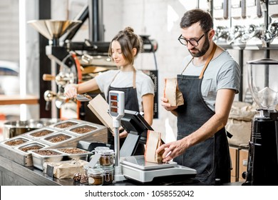 Two sellers in uniform filling bags with coffee beans working in the coffee store