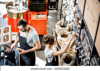 Two sellers in uniform filling and weighing bags with coffee in the coffee store. View from above