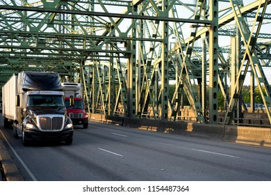 Two semi trucks of different capacity and size move along Columbia Interstate Bridge. One of their semi trucks is for long haul shipments, while the smaller one is intended for local transportation