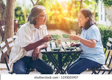 Two senior Asian or friends is drinking coffee and smiling or discussing future plan after retire while sitting on cafe. Mature couple enjoying coffee together. happy meeting senior club concept