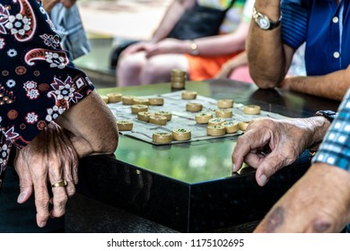 Two senior citizens playing chinese chess (Xiangqi) during their leisure time.