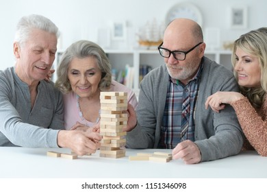 two senior couples playing with wooden blocks