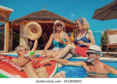 Two senior couples sunbathing, relaxing and having fun at the swimming pool on a hot sunny summer day, enjoying their vacation, drinking cocktails and cooling down in the pool