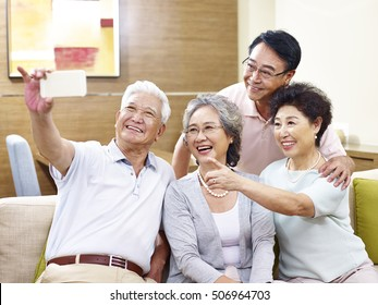 two senior couples taking a selfie on couch at home