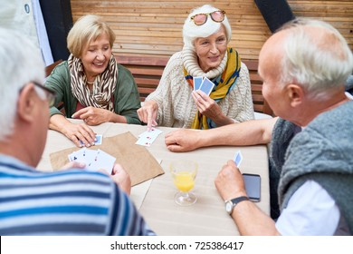 Two senior couples wearing warm clothes playing card with each other while gathered together at cozy small patio