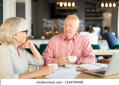 Two senior economists having tea-break in cafe and discussing some working points or ideas