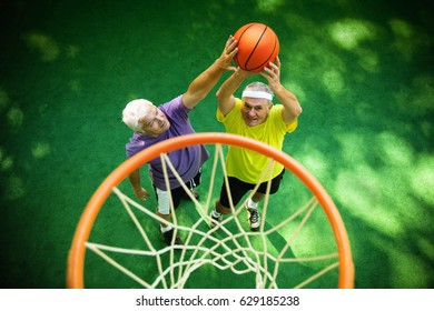 two senior friends playing basketball