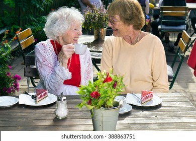 Two senior lady friends enjoying outdoor refreshments sitting at a table on a garden patio at a restaurant smiling and chatting in the sunshine.