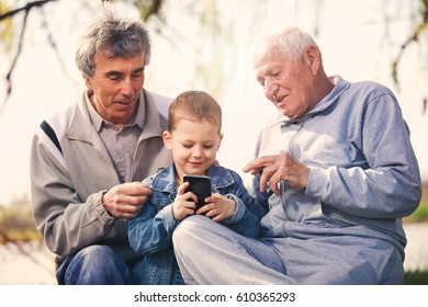 Two senior men and grandson using smart phone in the park