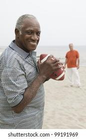 Two senior men playing american football on beach