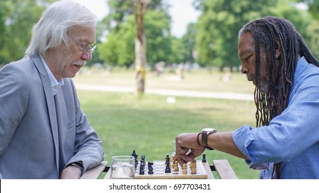 Two senior men playing a game of chess outdoors in the park