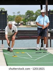 Two senior men playing opposing teams in a shuffleboard tournament.
