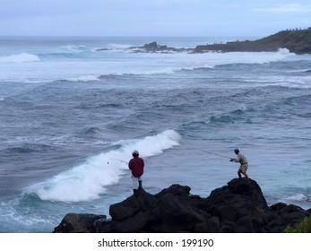 Two senior men surf fishing off the ocean rocks
