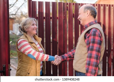 two senior neighbors man and woman takling to each other on sunny day near fence. They discuss important news