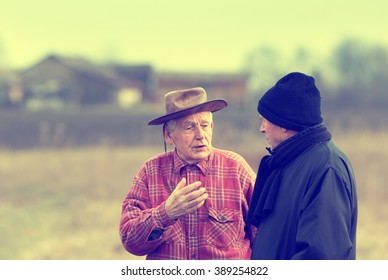 Two senior peasants talking on the farmland in winter time