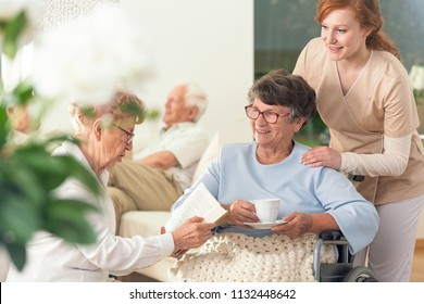 Two senior pensioners enjoying their leisure time together inside a private nursing home. Tender caretaker in uniform standing next to them