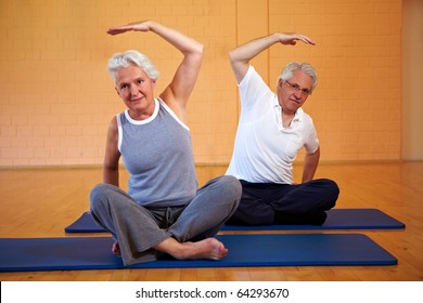 Two senior people doing gymnastics in a gym
