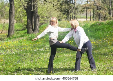 Two senior women doing stretching exercises in the park
