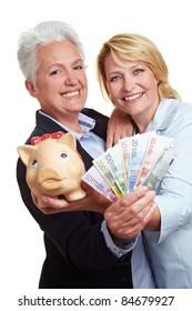 Two senior women with Euro money bills and piggy bank