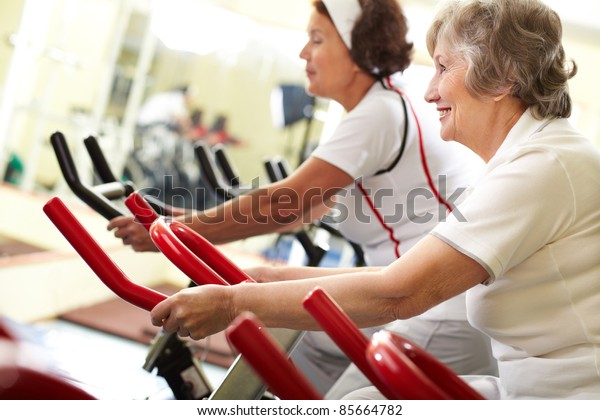 Two senior women exercising on training machines