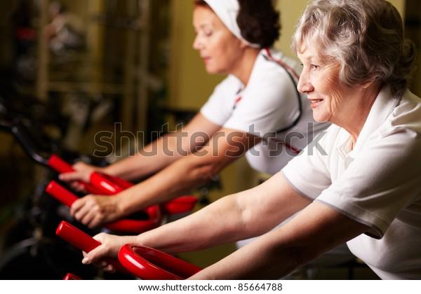 Two senior women training in gym