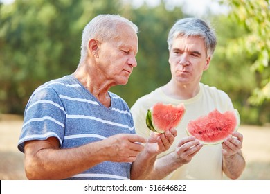Two seniors eating watermelon in summer