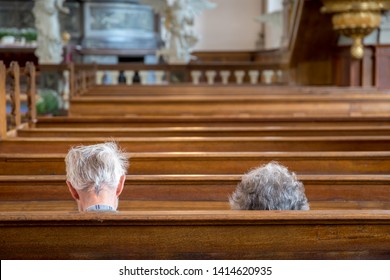 Two seniors (elderly couple) in an empty church, sitting in a pew.