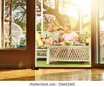 two seniors having dinner on patio.