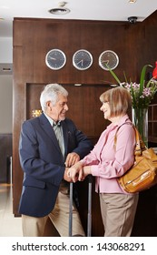 Two seniors waiting at hotel reception for check-in