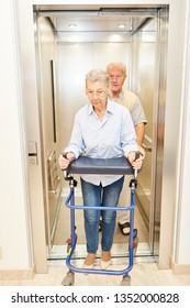 Two seniors with walkers in a lift in a rehab clinic or nursing home